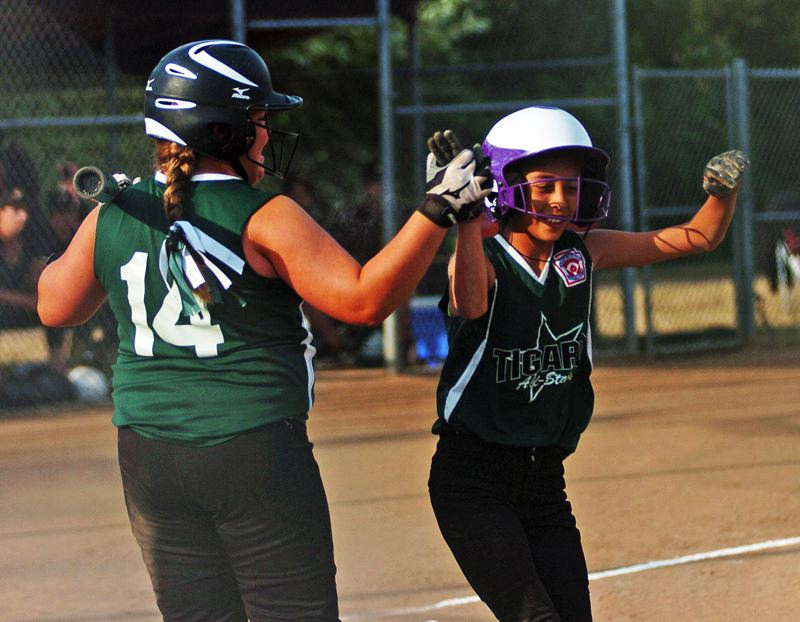 by: DAN BROOD - Riley White (right) gets a high-five from Victoria Vanderburg after scoring the game's first run.
