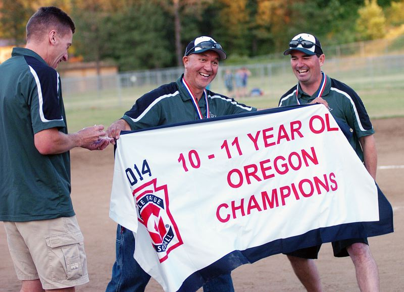 by: DAN BROOD - Tigard coaches (from left) Bill Gearin, Steven Dardis and Mark Torres stake claim to the state championship banner.