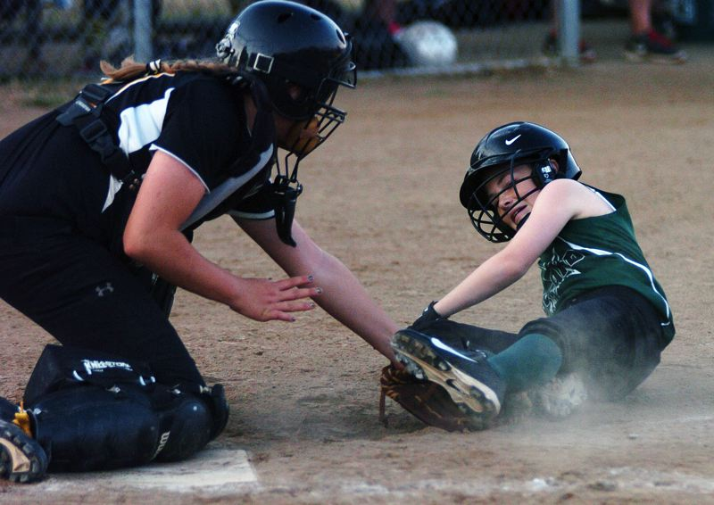 by: DAN BROOD - Tigard's Emily Torres comes up just short of home plate as she is tagged out by Centennial catcher Savannah Darling.