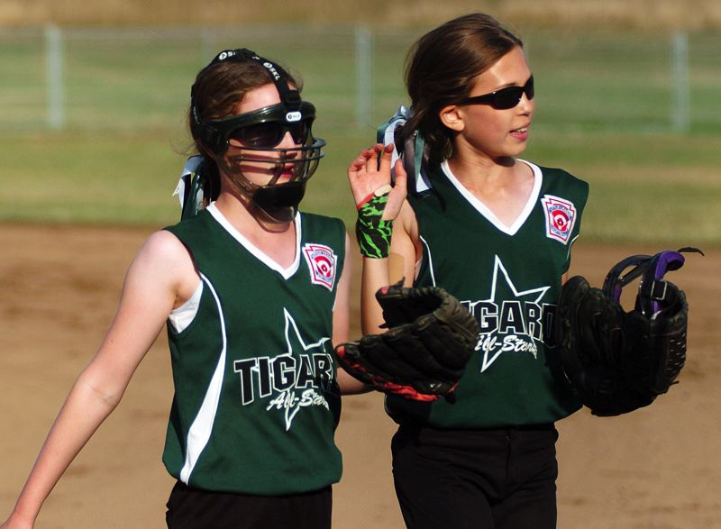 by: DAN BROOD - Tigard's Kaitlyn Gearin (left) and Elli Dardis head to the dugout after keeping Centennial scoreless in the bottom of the first inning.