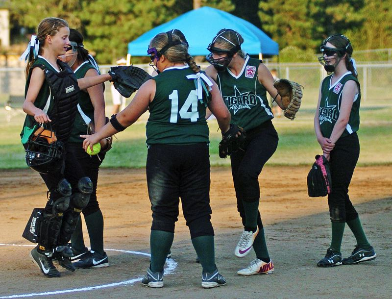 by: DAN BROOD - Tigard infielders, as well as catcher Grace Nelson (left) and pitcher Victoria Vanderburg (14), gather in the middle of the field.