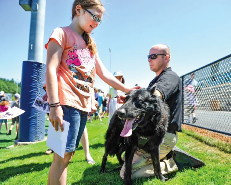 by: TIMES PHOTO: JOHN LARIVIERE - Avery Gaunt, 10, pets K-9 OfficerBarak as Officer Mike Bewersdorff signs autographs following the popular Beaverton Police Department K-9 Unit demonstration. The K-9 Unit will delight the crowd again on July 26 during the ninth annual Party in the Park.