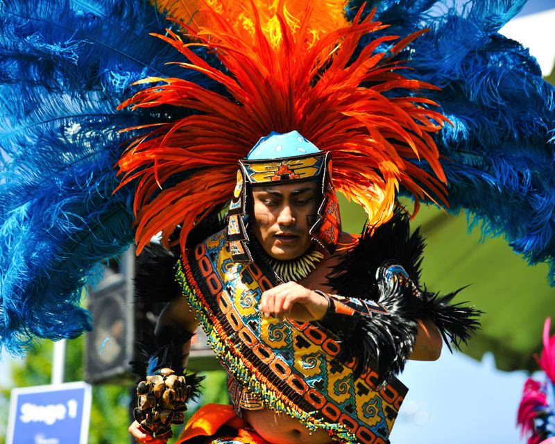 by: TIMES PHOTO: JOHN LARIVIERE - Huitzilopochtli dance troupe captain Jose Carlos performs a traditional Aztec dance honoring the sun while wearing a colorful headdress as part of the Beaverton International Celebration.