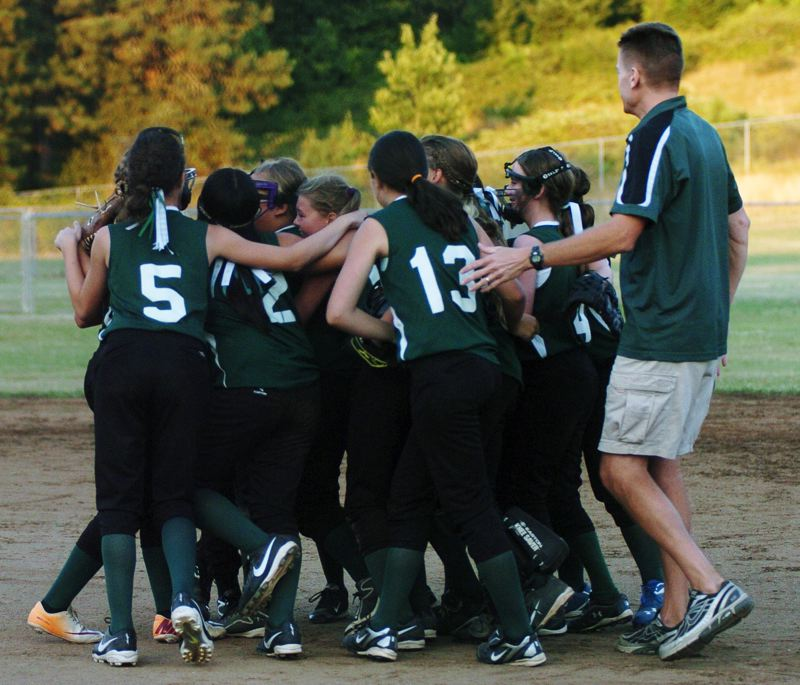 by: DAN BROOD - The Tigard Little League ages 10-11 all-star softball team has a group hug after the final out of the state championship game.