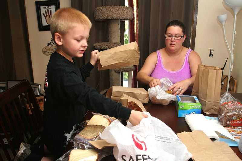 by: OUTLOOK PHOTO: JIM CLARK - Jackson Clark and his mom, Trisha, prepare and assemble lunches they offer to the homeless on the streets of Gresham. Each week, Jackson delivers between 10-14 sack lunches, containing a sandwich, fruit cup, cookie and bottle of water.