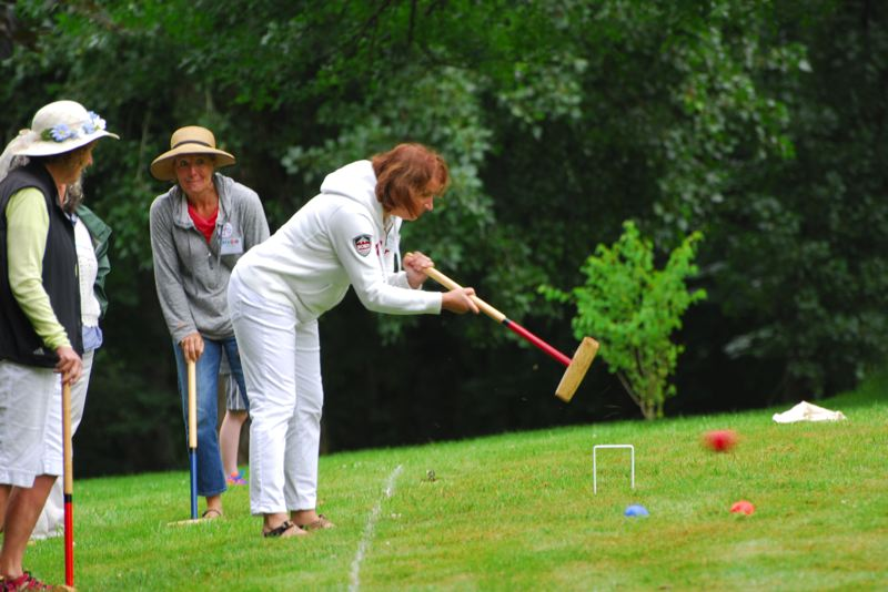 by: CONTRIBUTED PHOTO: MENUCHA RETREAT AND CONFERENCE CENTER - First Presbyterian church member Janet Starosciak and Cynthia Winter of Corbett watch Corbett's Sarah Van Haeften hit a hard one at Menucha's annual croquet tournament.