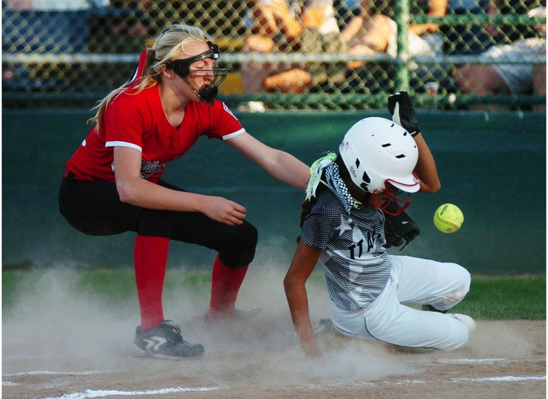 by: DAN BROOD - SHE'S SAFE -- Tigard/Tualatin City's Tia Cordts (right) scores on a wild pitch while Willow Creek's Grace Kimball looks to make a play in the second inning of Friday's district title game.