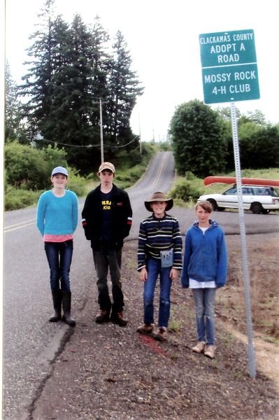 by: CONTRIBUTED: BARB HICKS - After working hard for weeks, the Mossy Rocks 4-H Club finally got their Adopt-a-Road highway sign. From left are Kate Glover, Austin Roberts, Dakota Glover and Alayna Roberts.