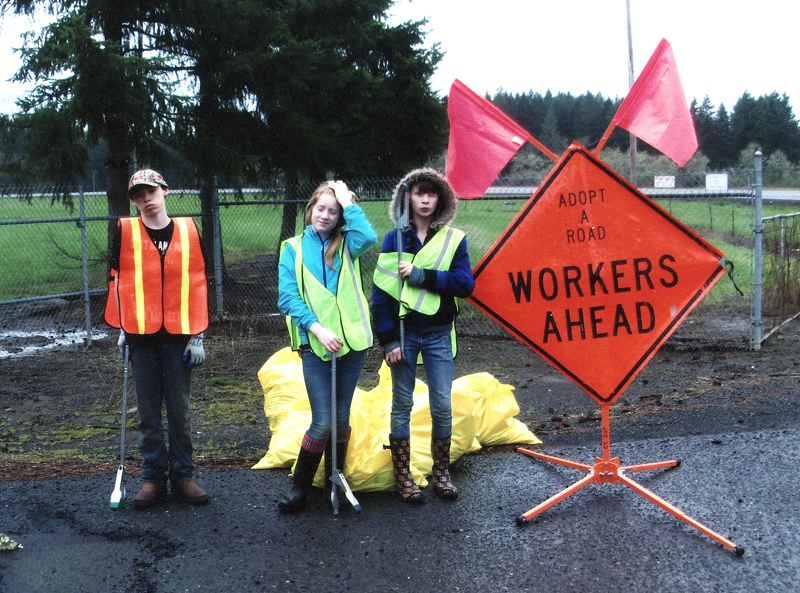 by: CONTRIBUTED: BARB HICKS - Members of the Mossy Rocks 4-H Club take a break after cleaning up a stretch of River Mill Road. From left are Austin Roberts, Kirstin Acardi and Alayna Roberts.