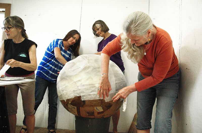 by: OUTLOOK PHOTO: BEVERLY CORBELL - From left, Nina Bradford, Lisa Brookshier, Carol Kleps and Jane Reid of the Estacada Area Arts Commission apply muslin strips to what will become the body of a giant paper mache puppet of Cocker Spaniel puppy for the Estacada Summer Celebration July 26.