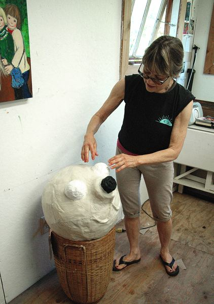 by: OUTLOOK PHOTO: BEVERLY CORBELL - Artist Nina Bradford checks on what will become the head of a giant paper mache puppet of a puppy dog for the Estacada Summer Celebration this weekend.