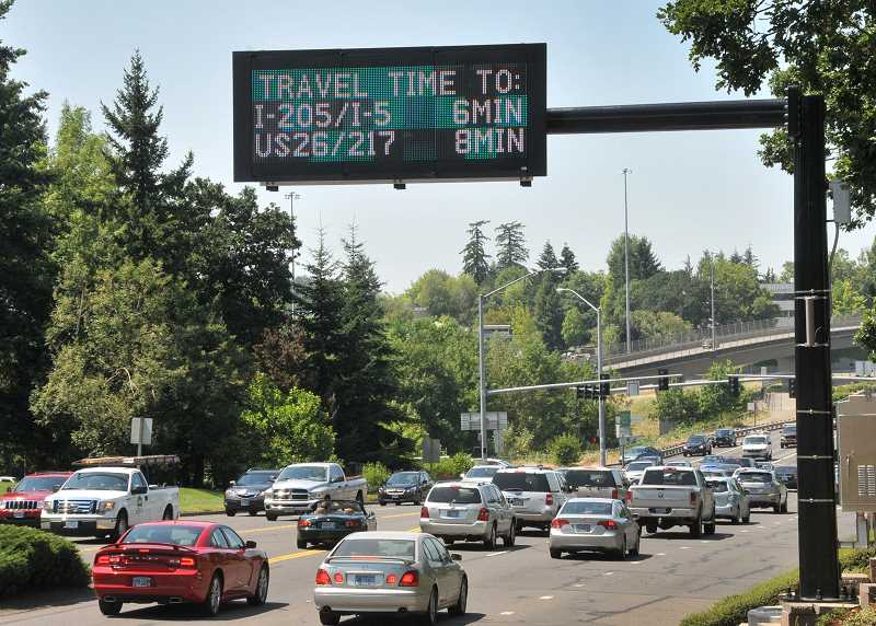 by: REVIEW PHOTO: VERN UYETAKE - New traffic signs from ODOT, including this one on Kruse Way near the intersection of I5 and 217, are designed to ease congestion by offering information on drive times.