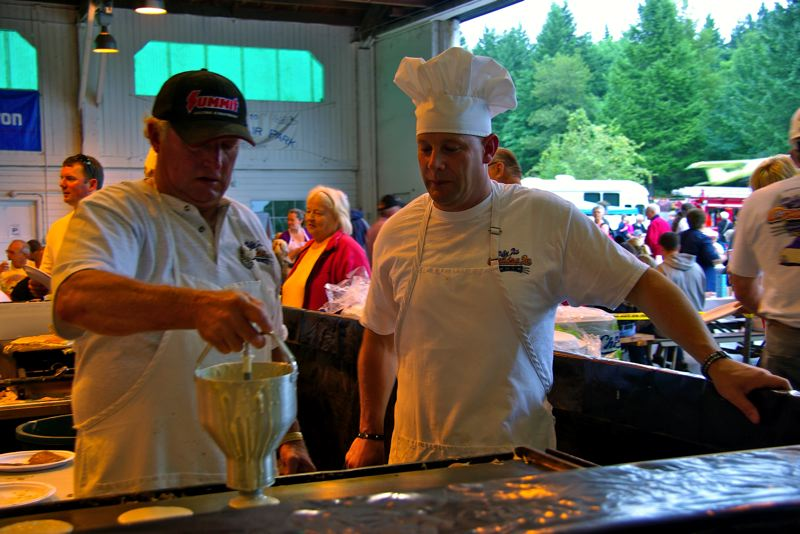 by: CONTRIBUTED PHOTO - Now Sandy Fire Division Chief Jason McKinnon learns the ropes of pancake making at last years breakfast.