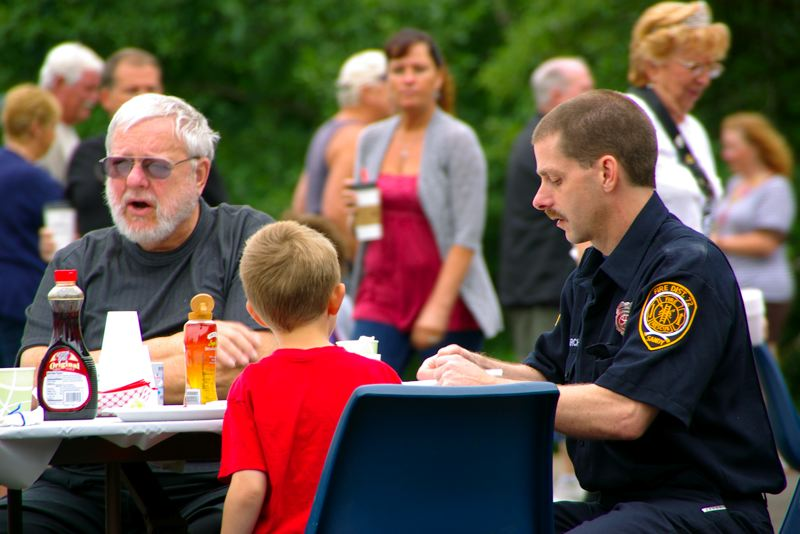 by: CONTRIBUTED PHOTO - Sandy Fire Volunteer Pat Archer and his son enjoy breakfast along with other community attendees.