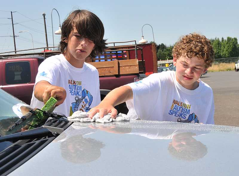 by: PAMPLIN MEDIA GROUP: VERN UYETAKE - Dylan Tiffany, left, and Thomas Skates work hard on a hot day to raise money for autism support through the Tiffany Autism Foundation.