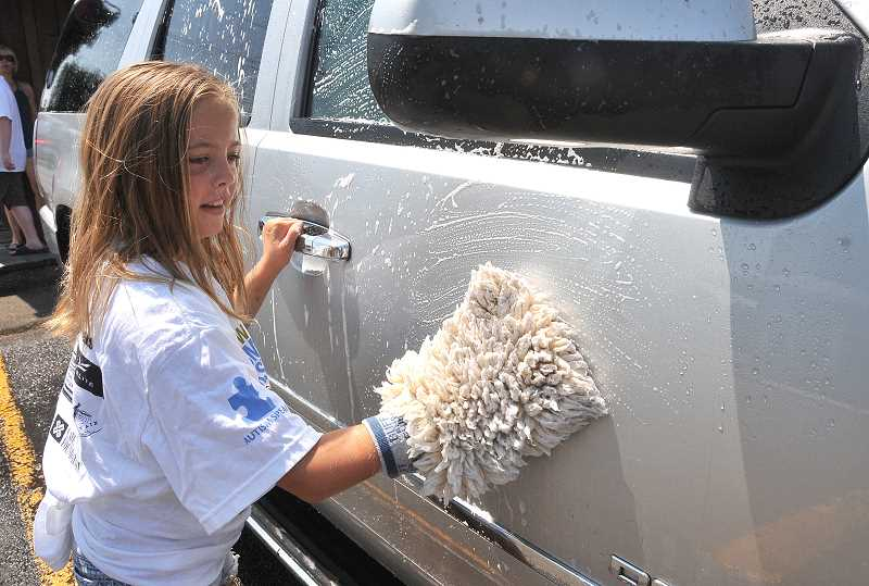by: PAMPLIN MEDIA GROUP: VERN UYETAKE - Kaia Kadel suds up a vehicle at a carwash fundraiser July 15 at Wanker's Corner on Stafford Road.