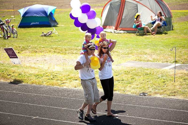 by: CONTRIBUTED PHOTO - Ryan and Melissa Law with their twin daughters Riley and Makena participated at a previous Estacada Relay for Life event.