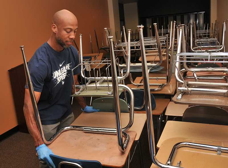by: REVIEW PHOTO: VERN UYETAKE - Custodian Dustin Toney hefts desks to make room for cleaning equipment in a Lake Oswego High School classroom.
