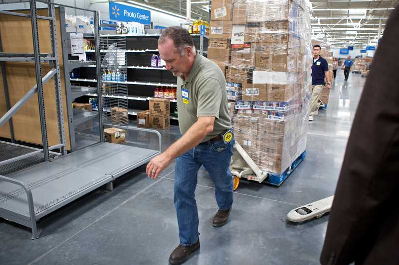by: TIMES PHOTO: JAIME VALDEZ - Hollis Bascom moves a pallet of boxes at the new Walmart supercenter on Southwest Dartmouth Street in Tigard. Both the Tigard store and the larger Sherwood supercenter will open at 7:30 a.m., Aug. 13.