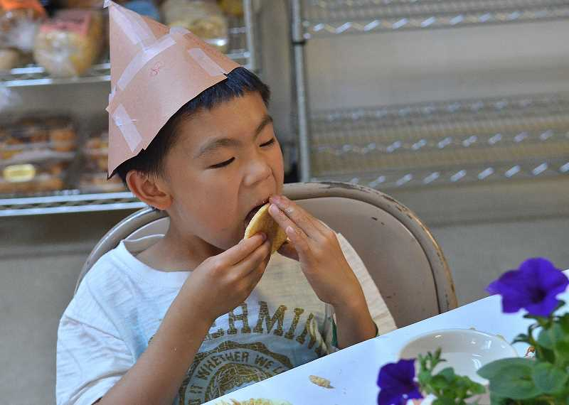 by: TIDINGS PHOTO: VERN UYETAKE - Ray Yoshmori, 7, enjoys a treat during Camp Namanu's Alice in Wonderland week July 2.