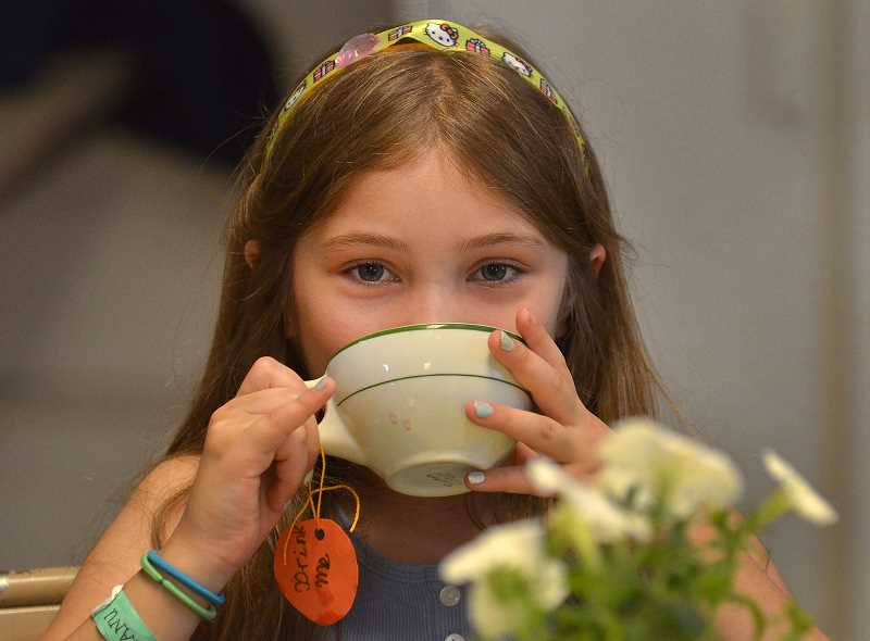 by: TIDINGS PHOTO: VERN UYETAKE - Emily Ronk, 8, demonstrates the proper way to drink tea.