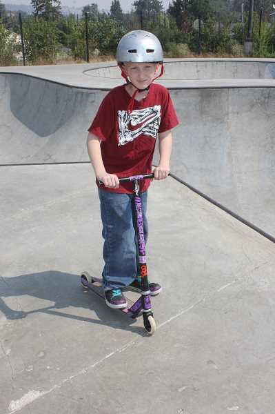 by: SUSAN MATHENY/MADRAS PIONEER - Cameron enjoys riding his scooter at the Madras Skate Park, the weekend before beginning a new treatment.