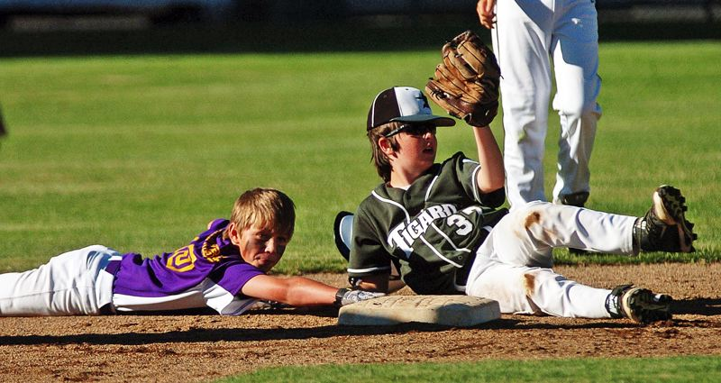 by: DAN BROOD - Tigard's Joey Myers (right) holds the ball up as Hermiston's Gavin Hunter scrambles back to the bag.