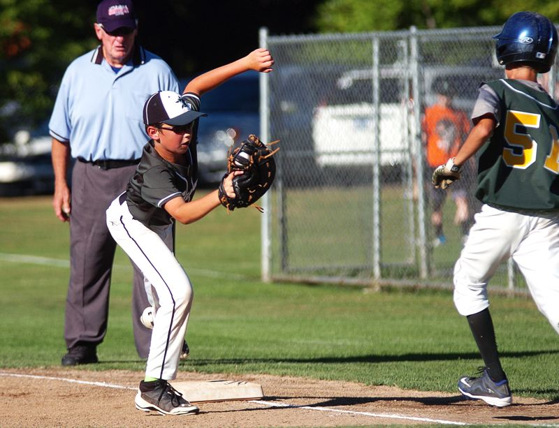 by: DAN BROOD - Tigard first baseman Aden Murphy stretches to try and stay on the bag in the semifinal win over Pendleton.