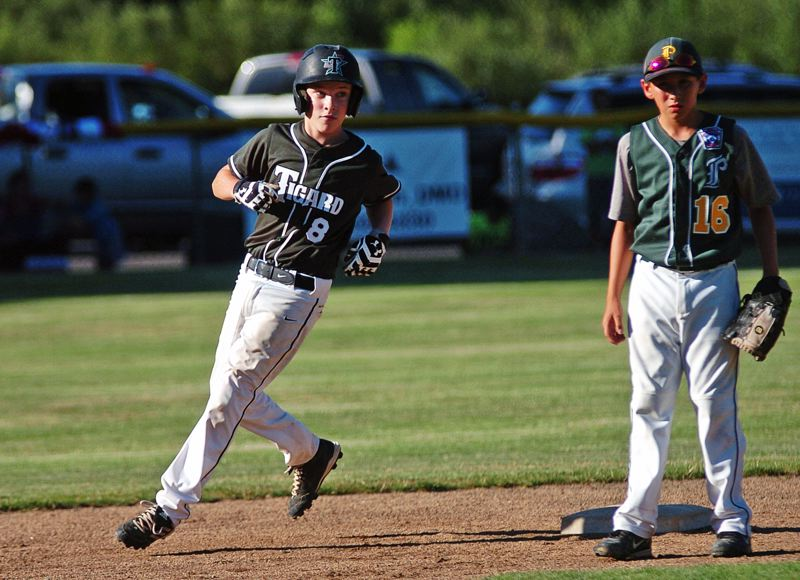 by: DAN BROOD - Tigard's Ty Penn circles around second base during the semifinal contest.