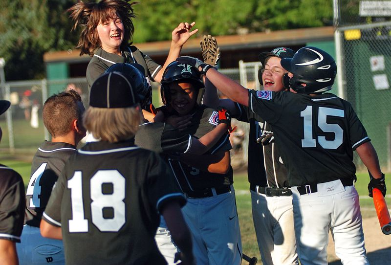 by: DAN BROOD - Tigard's Mike Brannon is mobbed by his teammates following his home run against Pendleton.