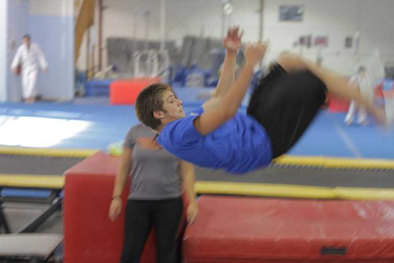 by: HILLSBORO TRIBUNE PHOTO: DAVID ROZA - Tumbling moves by Jeffrey Dicintio happen under the watchful eye of coach Cari Aurich. Here, he practices a front tuck.