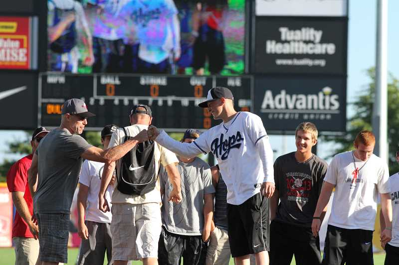 by: HILLSBORO TRIBUNE PHOTO: AMANDA MILES - Aaron Ahlstron (in Hops jersey) is greeted by Clackamas teammates and coaches on the field before he throws out the first pitch at last Thursdays Hillsboro Hops game. Ahlstrom, 18, a recent Clackamas High School graduate, is battling brain cancer.