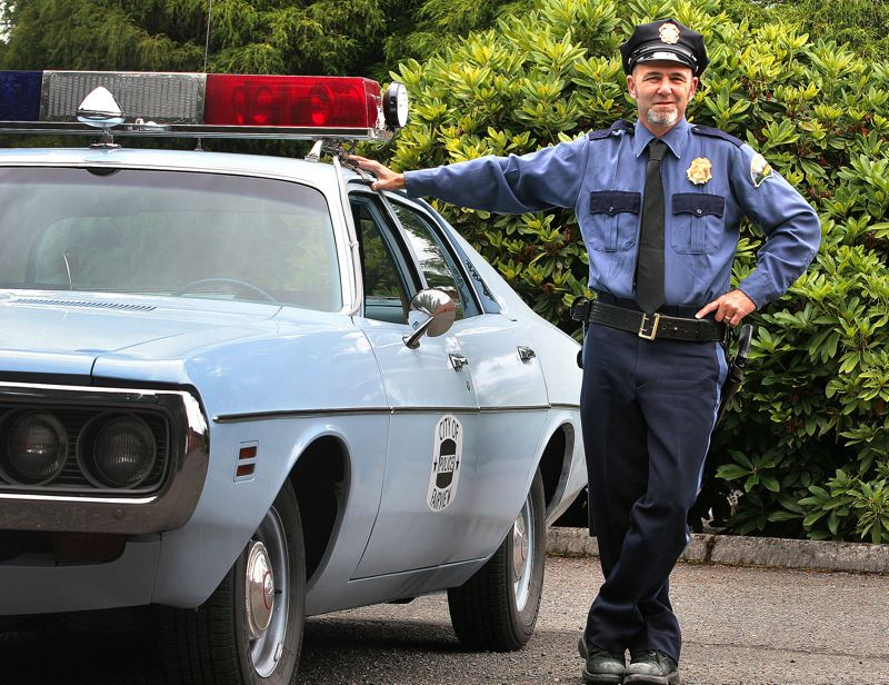 by: OUTLOOK PHOTO: JIM CLARK - Corbett resident Chad Olin stands beside his authentically restored 1971 Dodge  Coronet, replicating the vehicle once used by his grandfather, Oren Wes Olin, the city of Fairviews first police chief. The uniform, hat and law enforcement equipment also belonged to the elder Olin, who died in June 1982.