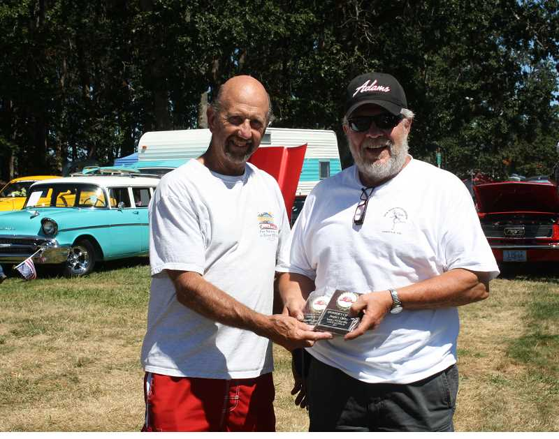 by: PEGGY SAVAGE - Jim Taylor, left, who organized Molalla first Cruise In, presents the People's Choice award to Gary Parham