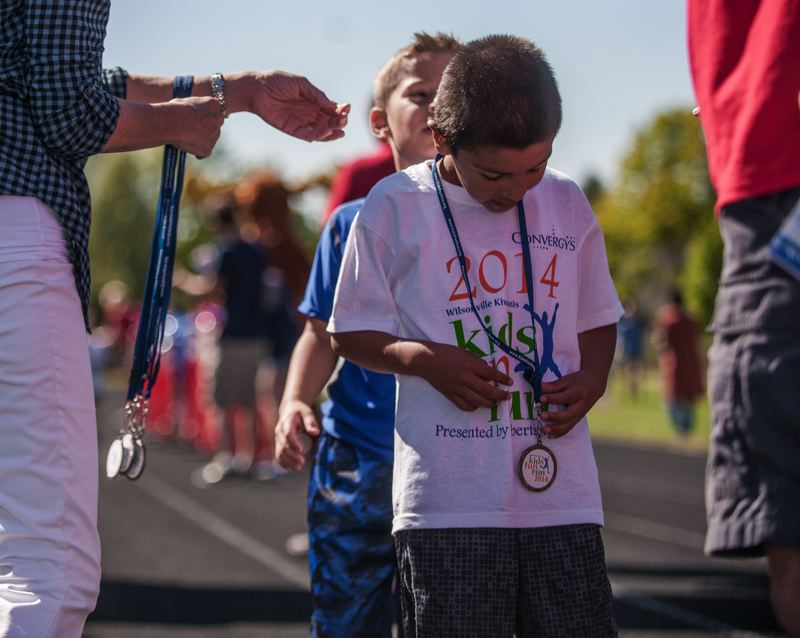 by: SPOKESMAN PHOTO: JOSH KULLA - A child examines his Wilsonville Kiwanis Kids Fun Run medal at the finish line Saturday at Wood Middle School.