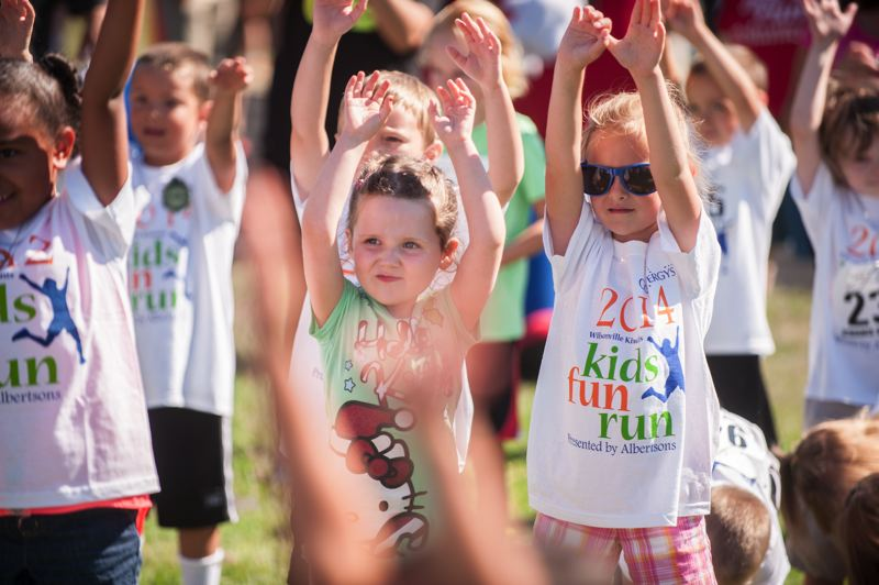 by: SPOKESMAN PHOTO: JOSH KULLA - Reach for the sky! Kids warm up prior to a heat July 26 at the WIlsonville Kiwanis Kids Fun Run.