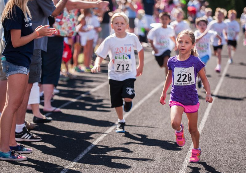 by: SPOKESMAN PHOTO: JOSH KULLA - Kids approach the finish line at the Wilsonville Kiwanis Kids Fun Run July 26 at Wood Middle School.