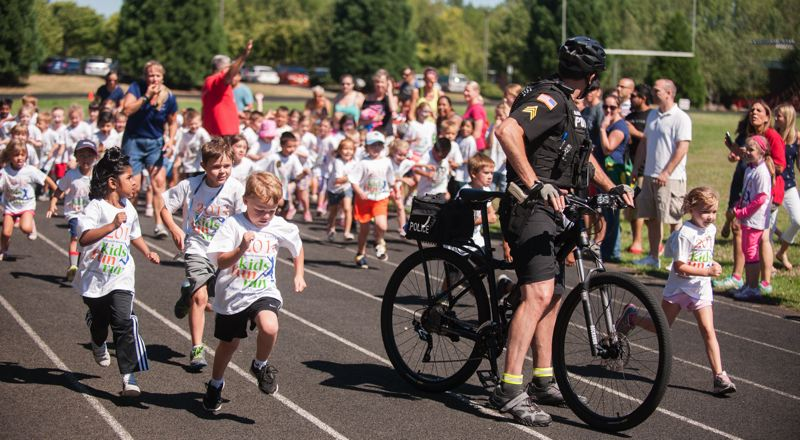 by: SPOKESMAN PHOTO: JOSH KULLA - This heat of kids had trouble with the start. But they still got their running in like the rest of the kids at the 2014 Wilsonville Kiwanis Kids Fun Run. At front is Wilsonville Police Sgt. Dan Kraus.