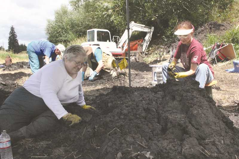 by: TYLER FRANCKE | WOODBURN INDEPENDENT - Archaeologists-in-training Cecily Brown, left, and Claudine Bailey, right, chat as they examine a pile of Pleistocene soil near Legion Park last week.