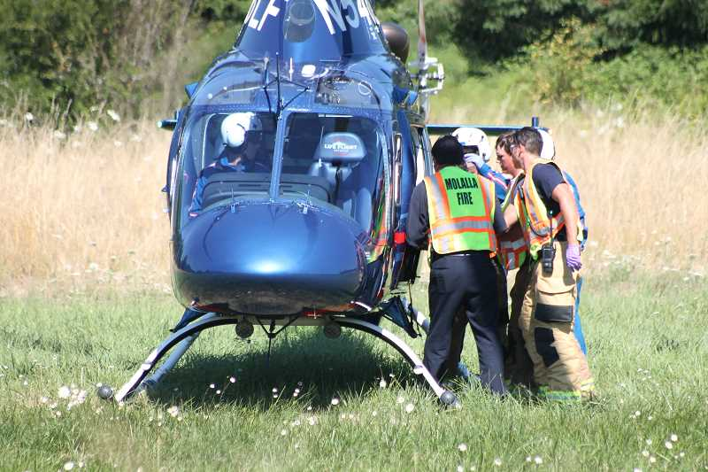 by: JIM BESEDA/MOLALLA PIONEER - Molalla Fire Department personnel place an injured driver inside the LifeFlight helicopter Monday following a head-on collision on Highway 213 near South Macksburg Road outside Molalla.