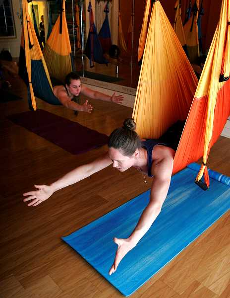 by: OUTLOOK PHOTO: JIM CLARK  - Aerial yoga uses swings made out of parachute material, designed to help students improve strength, balance and flexibility.