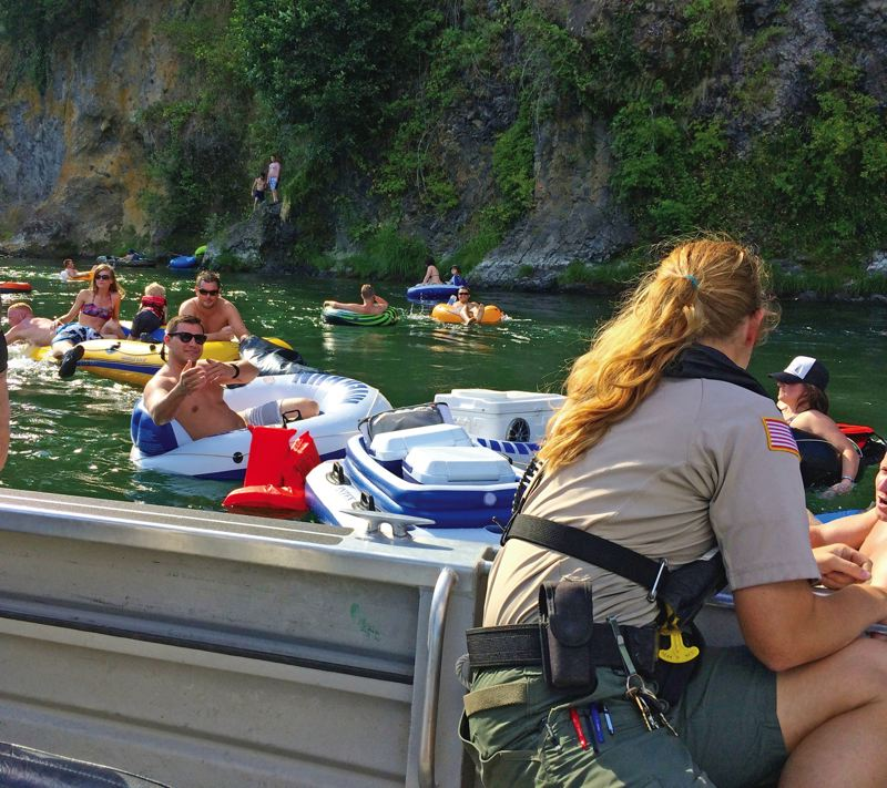 by: TRIBUNE PHOTO SHASTA KEARNS MOORE - Clackamas County Marine Services Officer Abigail Hunt helps ensure floater safety on the popular Clackamas River float from Barton to Carver Parks. Two people have drowned near this location in the past five years.