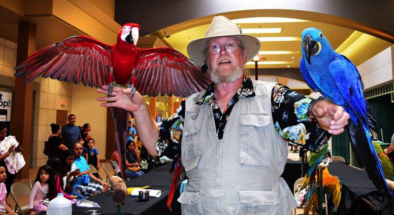 by: CONTRIBUTED PHOTO - Anderson with Zeus, a Greenwing Macaw parrot (on the left), and Sam, a Hyacinth Macaw, at a mall show in Salem.