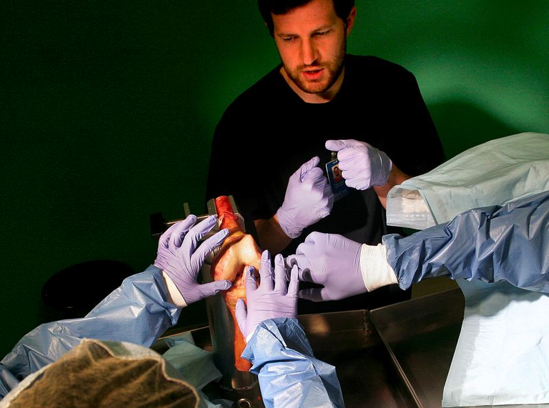 by: OUTLOOK PHOTO: JIM CLARK - Lab tech Tyler Laws instructs students to feel the surface of a healthy knee joint.