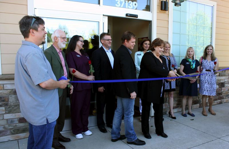 by: POST PHOTO: KYLIE WRAY - Sandy Area Chamber of Commerce members and Jeremy Pietzold performed a ribbon cutting outside of the new Fresenius Medical Care center Saturday.
