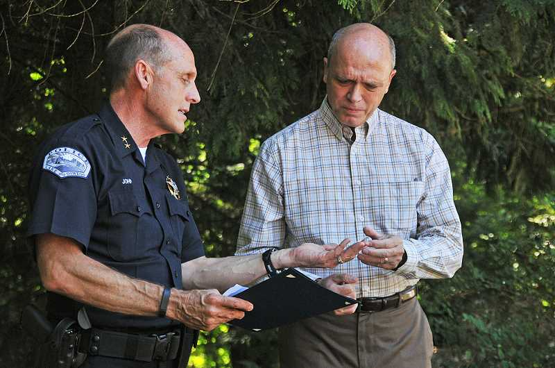 by: REVIEW PHOTO: VERN UYETAKE - Lake Oswego Police Chief Don Johnson presents former Portland City Commissioner Randy Leonard with the Chiefs Coin on Monday for his efforts to keep a distraught woman from committing suicide.