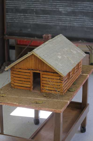 A log-cabin model of one of the early buildings now graces the Gales Creek School entryway.