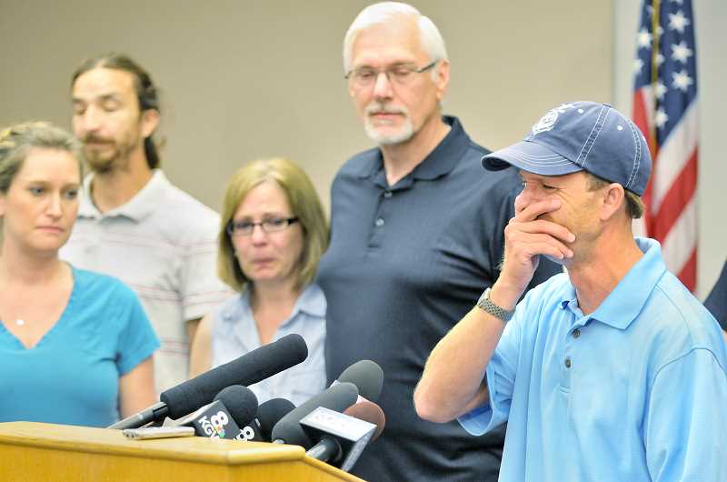 Photo Credit: GARY ALLEN - Kallen Huston, surrounded by friends and family, breaks down during a press conference held Monday at the Newberg Public Safety Building.