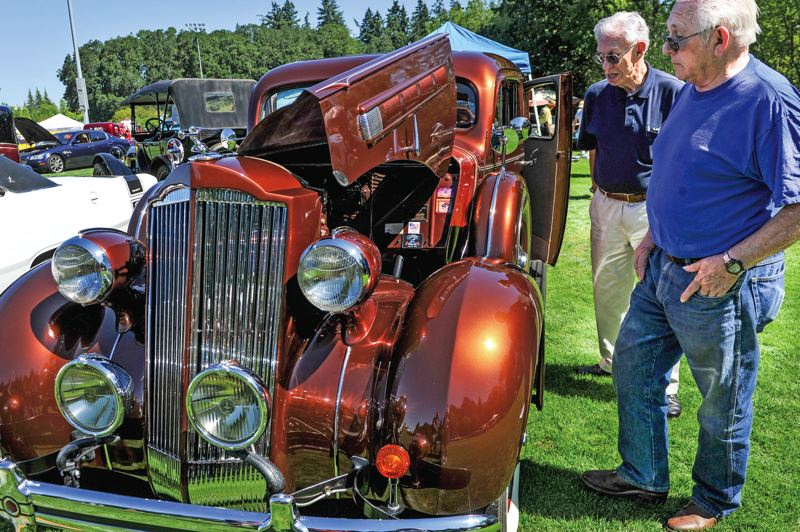 by: TIMES PHOTOS: JOHN LARIVIERE - Perry Weinberger and Bill Lucke check out a 1936 Packard touring sedan owned by Fred and Ruby Black of Aloha that was on display at The Classic at T-Hills car show during the Party in the Park.