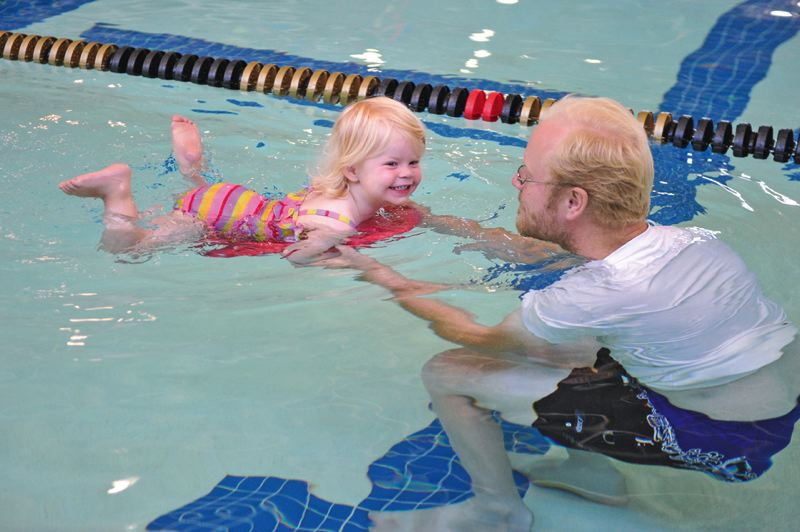 by: TIMES PHOTOS: JOHN LARIVIERE - Kevin Sanders of Beaverton helps his 26-month-old daughter Madelyn during the swimming portion of the Family Triathlon at the Tualatin Hills Aquatic Center.